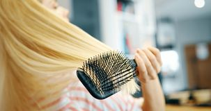 Attraktiv le kvinna som borstar hennes hår Royaltyfri Fotografi