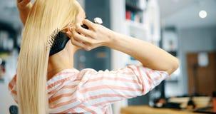 Attraktiv le kvinna som borstar hennes hår Fotografering för Bildbyråer
