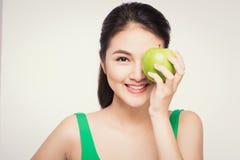 Attraktiv le ung asiatisk kvinna som äter det isolerade gröna äpplet Royaltyfri Bild
