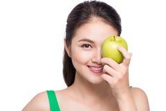 Attraktiv le ung asiatisk kvinna som äter det isolerade gröna äpplet Royaltyfri Fotografi