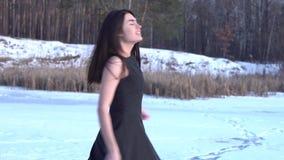 Attraktiv le ung brunettflicka för stående som omkring vänder i en svart klänning på en skoglandskapbakgrund arkivfilmer