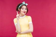 Attraktiv le utvikningsbrudflicka i gul klänning som pekar upp fotografering för bildbyråer