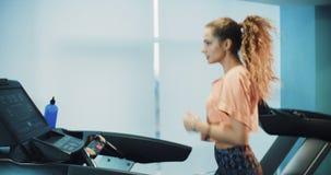 Attraktiv lockig flickaspring på trampkvarnen i sportidrottshallen stock video