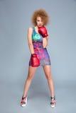 Attraktiv lockig ung kvinna som bär röda boxninghandskar royaltyfri foto