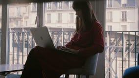 Attraktiv lyckad frilans- affärskvinna som använder bärbara datorn som sitter på det härliga Paris lägenhetfönstret på semester arkivfilmer