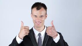 Attraktiv lyckad le affärsman med tummen upp Arkivfoton