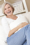 Attraktiv lycklig hög kvinna som hemma skrattar Arkivfoton
