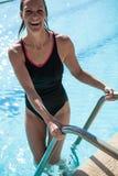 Attraktiv lycklig kvinnlig simmare på stege på kantsimbassängen arkivfoton