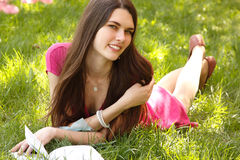 Attraktiv lycklig le tonårig flickaläsebok för student på gräsplan Royaltyfri Bild