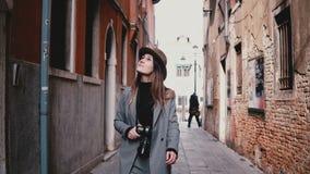 Attraktiv lycklig yrkesmässig kvinnlig fotograf som går med kameran som ler längs den härliga gamla gatan i Venedig Italien lager videofilmer