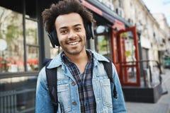 Attraktiv mörkhyad le grabb med borstet som lyssnar till musik, medan gå på gatan och att vara i bra lynne och royaltyfri fotografi