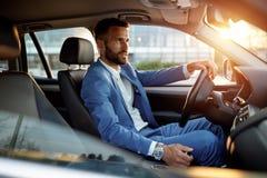 Attraktiv man i affärsdräkten som kör bilen
