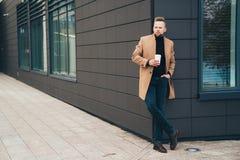 Attraktiv man i moderiktigt brunt lag och coffe i hans hand som poserar nära affärsmitt arkivfoto