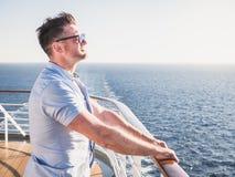 Attraktiv man i solglasögon på det bästa däcket av ett kryssningskepp royaltyfria bilder