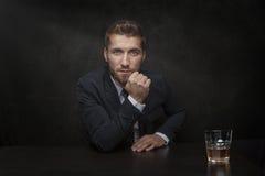 Attraktiv man med ett exponeringsglas av whisky Arkivbild