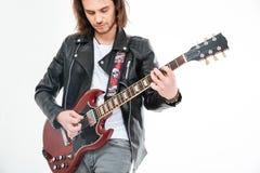 Attraktiv man med långt hår som spelar den elektriska gitarren genom att använda medlaren arkivbilder