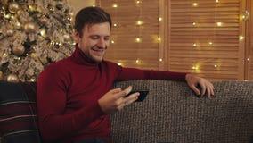 Attraktiv man som använder smartphonen som sitter på soffan, messaging som ler i dekorerad lägenhet nära trevligt Honom hållande  stock video