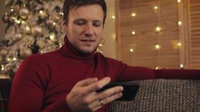 Attraktiv man som använder smartphonen som sitter på soffan, messaging som ler i dekorerad lägenhet nära trevligt Honom hållande  lager videofilmer