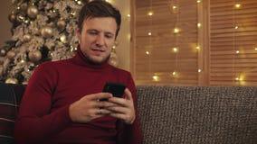 Attraktiv man som använder smartphonen som sitter på soffan, messaging som ler i dekorerad lägenhet nära trevligt jul min version arkivfilmer