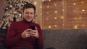 Attraktiv man som använder smartphonen som sitter på soffan, messaging som ler i dekorerad lägenhet nära trevligt jul min version stock video