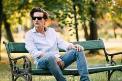 Attraktiv man som bara sitter på bänken med mobiltelefonen royaltyfri fotografi
