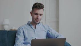 Attraktiv man som direktanslutet hemma arbetar på bärbar datordatoren Manlig framsida för leende som bläddrar rengöringsduk på da arkivfilmer