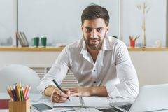 Attraktiv man som gör skrivbordsarbete Royaltyfria Foton