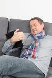 Attraktiv man som kopplar av på hans soffa Royaltyfri Foto