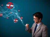 Attraktiv man som röker den farliga cigaretten med inget - röka undertecknar Arkivfoto