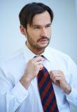 Attraktiv man som rätar ut hans tie Arkivbild