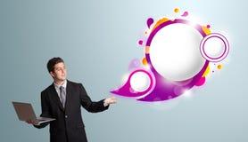 Attraktiv man som rymmer en bärbar dator och framlägger abstrakt anförande b Royaltyfri Fotografi