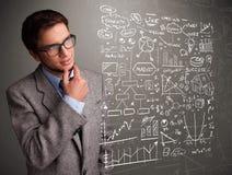 Attraktiv man som ser aktiemarknadgrafer och symboler Arkivfoto