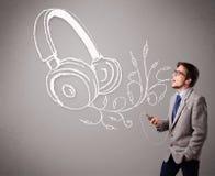 Attraktiv man som sjunger och lyssnar till musik med det abstrakt huvudet Royaltyfria Foton