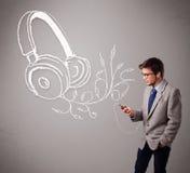 Attraktiv man som sjunger och lyssnar till musik med det abstrakt huvudet Royaltyfri Bild