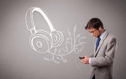 Attraktiv man som sjunger och lyssnar till musik med det abstrakt huvudet Arkivbild