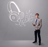 Attraktiv man som sjunger och lyssnar till musik med det abstrakt huvudet Royaltyfri Fotografi