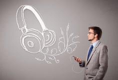 Attraktiv man som sjunger och lyssnar till musik med det abstrakt huvudet Arkivfoton