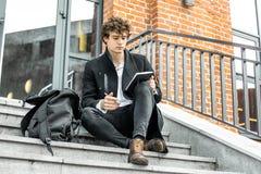 Attraktiv man som skriver anmärkningar i hans notepad på röda bricked byggande moment royaltyfria foton
