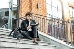 Attraktiv man som skriver anmärkningar i hans notepad på röda bricked byggande moment arkivfoton