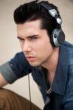 Attraktiv man som utomhus lyssnar till musik på hörlurar Royaltyfria Bilder