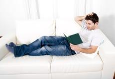 Attraktiv manläsebok eller studera på soffan Royaltyfri Bild