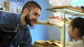 Attraktiv manlig bagare som lite talar till flickan på hans bagerilager arkivbilder