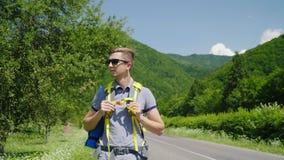 Attraktiv manturist med en ryggsäck som promenerar vägen på en bakgrund av gröna berg Turism som är sund och lager videofilmer