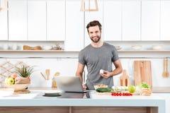 Attraktiv matlagning för ung man med plastbunken arkivfoton