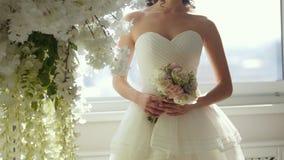 Attraktiv modell i bröllopsklänning med buketten för brud` s arkivfilmer