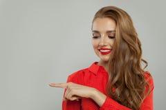 Attraktiv modell med makeup och långt lockigt hår som åt sidan pekar och ler på vit bakgrund fotografering för bildbyråer