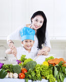 Attraktiv moder och son som förbereder en sallad Royaltyfri Bild