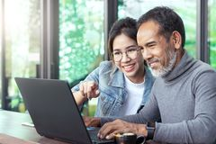 Attraktiv mogen asiatisk man med det vita stilfulla korta skägget som ser bärbar datordatoren med den tonårs- kvinnan för ögonexp royaltyfria bilder