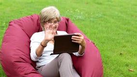 Attraktiv mogen kvinna som använder den digitala minnestavlan i en parkera arkivfilmer