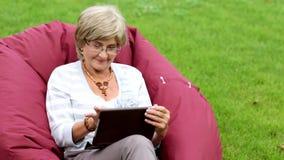 Attraktiv mogen kvinna som använder den digitala minnestavlan i en parkera stock video